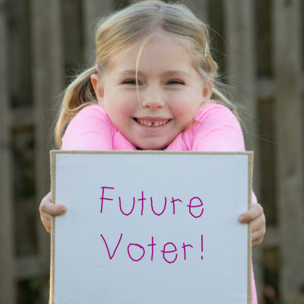 girl holding sign that says future voter